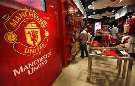 Manchester United fans from Thailand look inside a souvenir shop in Bangkok August 18, 2011. REUTERS/Chaiwat Subprasom