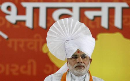 Gujarat's Chief Minister Narendra Modi wears an Indian traditional turban as he sits on the first day of his fast at a convention centre in Ahmedabad September 17, 2011. The words in the background read ''Emotion''. REUTERS/Amit Dave/Files