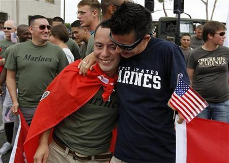 Active duty U.S. Marine corporal Jime Rindon (L) from Camp Pendleton receives a hug as he prepares to march with active and non-active U.S. military personnel who are participating for the first time in San Diego's Gay Pride Parade in San Diego, July 16, 2011. REUTERS/Mike Blake