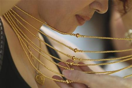 A customer tries on a gold necklace at a gold shop in Hanoi August 23, 2011. REUTERS/Kham