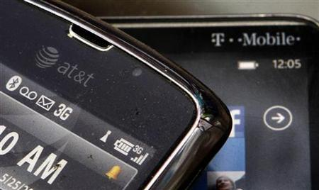 An AT&T mobile device is seen alongside a T-Mobile mobile device at a cellular store in Los Angeles, in this posed picture taken August 31, 2011. REUTERS/Danny Moloshok