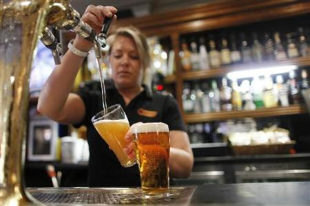 A barmaid pours a glass with beer produced by Fosters at the Occidental Hotel in central Sydney June 21, 2011. REUTERS/Tim Wimborne
