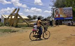 <p>A woman with her child rides her cycle past a destroyed building and a billboard featuring a picture of Sri Lankan President Mahinda Rajapakse in war-hit Kilinochchi town on September 7, 2011. More than two years since Sri Lanka's 25-year-old conflict ended, mental health experts say thousands of survivors are living in torment typical of war survivors -- haunted by memories of the final months of fighting between the separatist Liberation Tigers of Tamil Eelam (LTTE) and government forces. REUTERS/ALERTNET/Nita Bhalla</p>