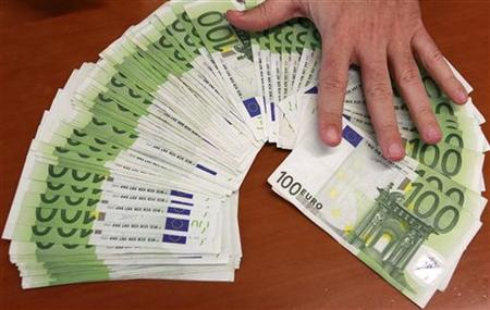 A bank employee spreads out euro notes at a bank branch in Madrid January 13, 2011. REUTERS/Andrea Comas