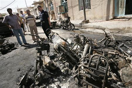 Residents look at burnt motorbikes at the site of multiple bomb attacks in Kerbala, 80 km (50 miles) southwest of Baghdad September 25, 2011. REUTERS/Mushtaq Muhammed