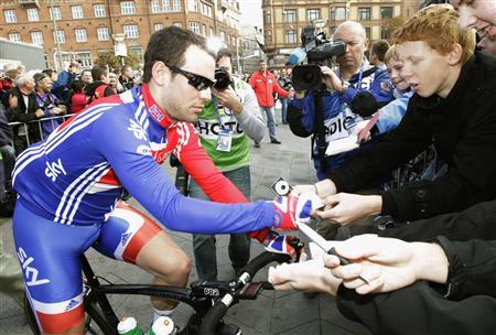 Mark Cavendish of Britain signs an autograph at the start of the men's road race elite event at the UCI World cycling championships in Copenhagen September 25, 2011. REUTERS/Denis Balibouse