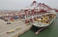 <p>Trucks unload shipping containers from a cargo ship at Qingdao port in Qingdao, Shandong province September 2, 2011. REUTERS/Stringer</p>
