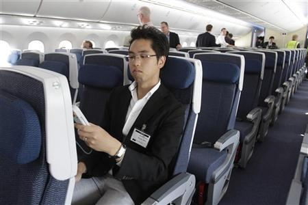 All Nippon Airway (ANA) employee Yong Choi looks at the entertainment controller while seated in the first Boeing 787 Dreamliner to be delivered to the Japanese airline at Boeing's Everett factory August 6, 2011. REUTERS/Robert Sorbo