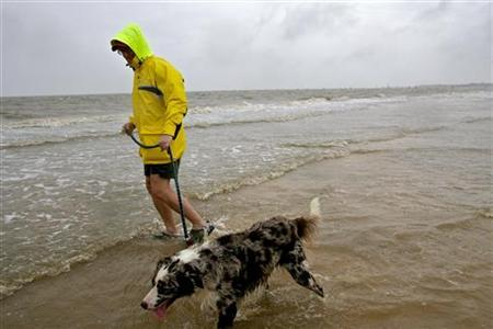 Brian Stanford walks with his dog on the beach in Bay St. Louis, Mississippi, September 3, 2011. REUTERS/Dan Anderson