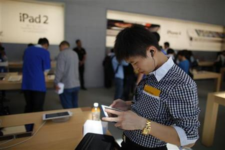 A man looks at an Apple iPad 2 at the company's new store in Nanjing Road, Shanghai September 23, 2011. The store is Apple's fifth and largest in mainland China. REUTERS/Aly Song