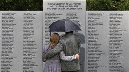 A couple shelters from the rain under an umbrella as they look at the main headstone in the Lockerbie air disaster memorial garden in Lockerbie, Scotland, August 19, 2010. REUTERS/David Moir