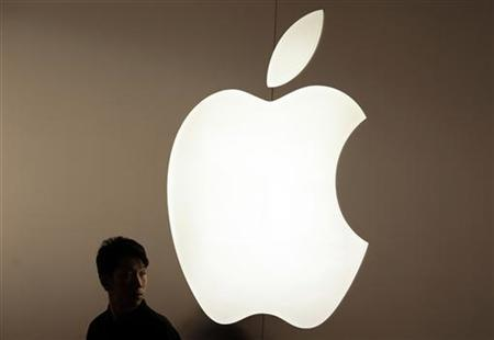 A security guard stands in front of an Apple logo during the inauguration of the company's new store in Nanjing Road, Shanghai September 23, 2011. The store is Apple's fifth and largest in mainland China. REUTERS/Aly Song (