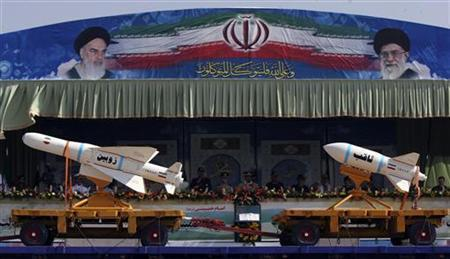 EDITORS' NOTE: Reuters and other foreign media are subject to Iranian restrictions on their ability to report, film or take pictures in Tehran. A military vehicle carrying Iranian Zoobin smart bomb (L) and Sagheb missile under pictures of Iran's Supreme Leader Ayatollah Ali Khamenei (R) and Late Leader Ayatollah Ruhollah Khomeini during a parade to commemorate the anniversary of the Iran-Iraq war (1980-88), in Tehran September 22, 2011. REUTERS/Stringer