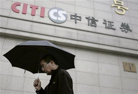 A man walks by the logo of CITIC Securities at a branch of the security brokerage house in Beijing March 30, 2010. REUTERS/Christina Hu