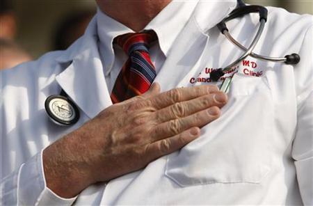 A doctor puts his hand over his chest during a ''House call'' rally against proposed healthcare reform legislation on Capitol Hill, November 5, 2009. REUTERS/Kevin Lamarque