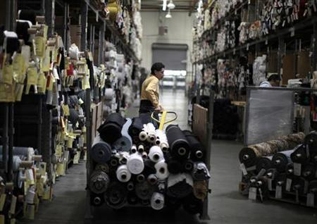 A worker wheels rolls of cloth in Los Angeles, California June 30, 2011. REUTERS/Lucy Nicholson