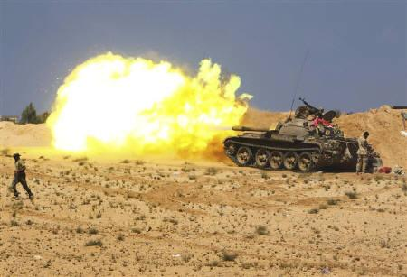 Anti-Gaddafi fighters fire from tanks during clashes with pro-Gaddafi forces near Sirte, September 28, 2011. REUTERS/Asmaa Waguih