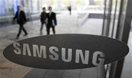 People walk behind a glass window bearing the logo of Samsung Electronics at the company's headquarters in Seoul November 6, 2009. REUTERS/Choi Bu-Seok