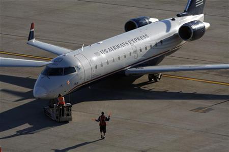 Ground crew help a U.S. Airways aircraft depart terminal 4 at Phoenix Sky Harbor International Airport in Phoenix, April 8, 2010. REUTERS/Joshua Lott