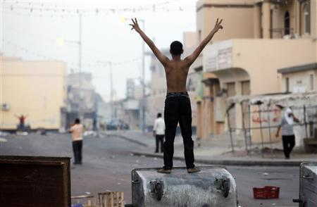 A protester standing on a garbage container shouts anti-government slogans as anti-government protesters try to get back to Manama's Farook Junction, also known as Pearl Square, in Karanna, west of Manama, September 23, 2011. REUTERS/Hamad I Mohammed