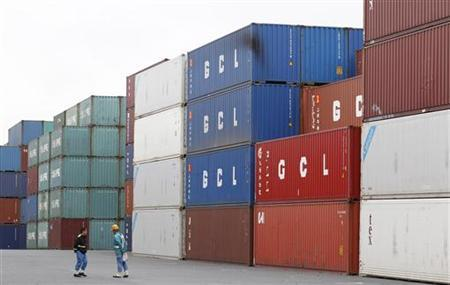 Workers stand in front of container at an industrial port in Tokyo July 21, 2011. REUTERS/Kim Kyung-Hoon