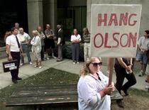 <p>A protestor carries a plackard as spectators line up outside a Surrey courthouse to watch the judicial review of convicted serial killer Clifford Olson, August 18, 1997. REUTERS/Jeff Vinnick</p>