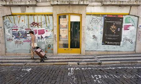 A woman pulls her shopping trolley in front of a closed shop in central Lisbon August 11, 2011. REUTERS/Jose Manuel Ribeiro