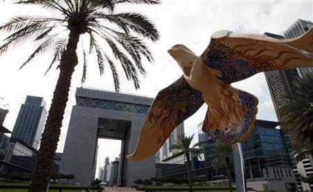 The sculpture of a falcon is seen in front of the Dubai International Financial Exchange building (2nd L) in Dubai, December 16, 2009. REUTERS/Mosab Omar
