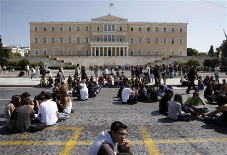 High-school students sit on a road during a protest march against economic austerity and planned education reforms in Athens, October 3, 2011. REUTERS/John Kolesidis