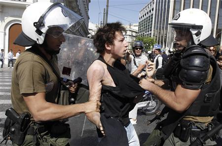 A high-school student is detained by riot police during a protest march against economic austerity and planned education reforms in Athens October 3, 2011. REUTERS/John Kolesidis