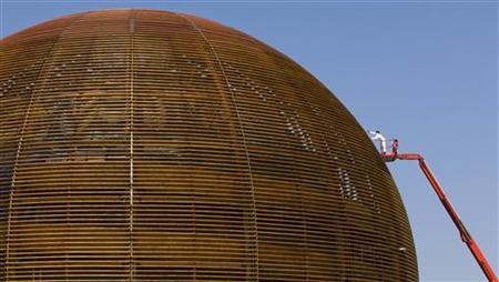 A man sprays varnish on the wooden globe next to the entrance of the European Organization for Nuclear Research (CERN) in Meyrin near Geneva September 9, 2009. REUTERS/Valentin Flauraud