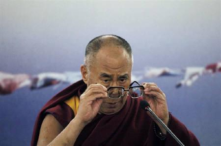 Tibet's exiled spiritual leader the Dalai Lama puts on his prescription glasses during a news conference in Sao Paulo September 16, 2011. REUTERS/Nacho Doce