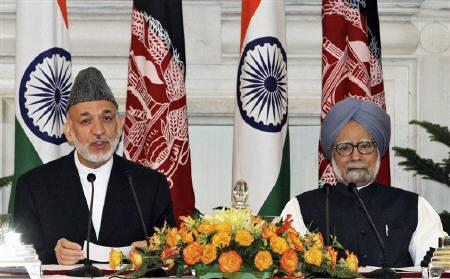 Afghanistan's President Hamid Karzai (L) speaks with the media as India's Prime Minister Manmohan Singh watches after signing a joint statement at Hyderabad House in New Delhi October 4, 2011. REUTERS/B Mathur