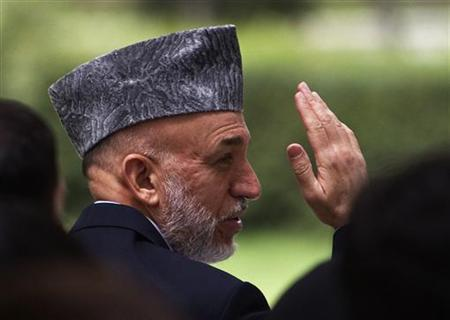 Afghan President Hamid Karzai waves before addressing a group of students who will be sent to India and Turkey for educational purposes, at the presidential palace in Kabul August 14, 2011. REUTERS/Ahmad Masood