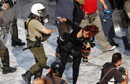 A riot policeman punches Greek photojournalist Tatiana Bolari during a demonstration in Athens' Syntagma (Constitution) square October 5, 2011. REUTERS/Yannis Behrakis