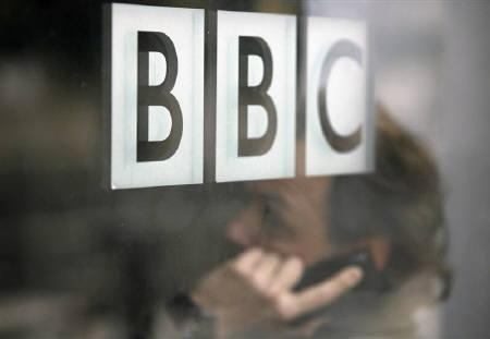 A man talks on a mobile phone inside the BBC headquarters in London November 21, 2008. .  REUTERS/Andrew Winning/Files