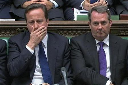 A still image from video shows Prime Minister David Cameron (L) and Defence Minister Liam Fox listening to questions after announcing the UK government's defence spending plans at parliament in London October 19, 2010. REUTERS/Parbul TV via Reuters TV
