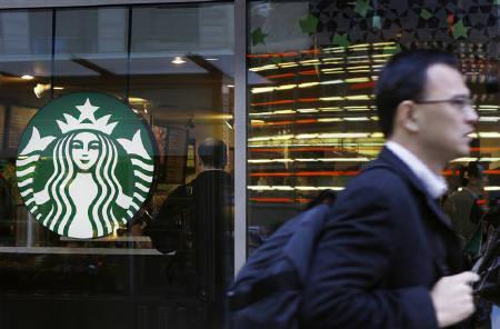 A pedestrian walks past the Starbucks logo on a store in Times Square in New York March 8, 2011. REUTERS/Lucas Jackson