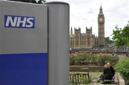 A National Health Service sign is seen in the grounds of St Thomas' Hospital, in front of the Houses of Parliament in London June 7, 2011. REUTERS/Toby Melville