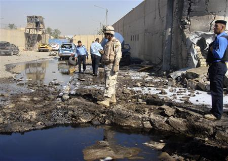A soldier and policemen inspect the site of a bomb attack at a police station in Baghdad's Hurriya district October 12, 2011. REUTERS/Stringer