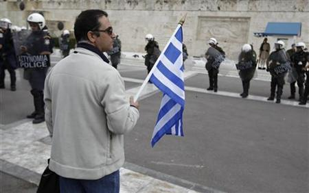 A protester stands in front of a police formation during a protest against planned wage cuts outside the parliament in Athens October 11, 2011. REUTERS/Yiorgos Karahalis
