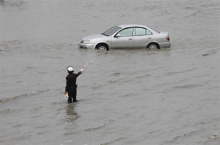A traffic policeman gestures to a car as he directs traffic along a flooded street in Nonthaburi province on the outskirts of Bangkok October 12, 2011. REUTERS/Chaiwat Subprasom