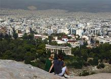 <p>Tourists sit on a hill overlooking Athens outside the archaeological site of the Acropolis due to a 48-hour strike by Culture Ministry employees, October 13, 2011. REUTERS/Yannis Behrakis</p>