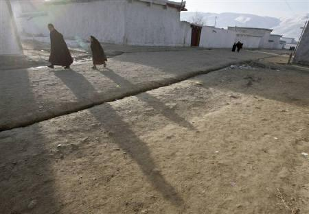 Ethnic Tibetan monks walk in the early morning at a monastery in Aba, Sichuan province, February 18, 2008. REUTERS/Reinhard Krause/Files