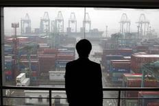 <p>An employee views the Port of Shanghai from an office window, January 19, 2011. REUTERS/Carlos Barria</p>