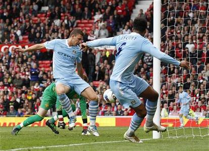 Manchester City's Edin Dzeko (L) scores against Manchester United during their English Premier League soccer match at Old Trafford in Manchester, northern England, October 23, 2011. REUTERS/Darren Staples