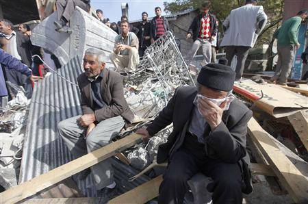 Survivors gather around a collapsed building in Ercis, near the eastern Turkish city of Van, October 24, 2011. REUTERS/Osman Orsal