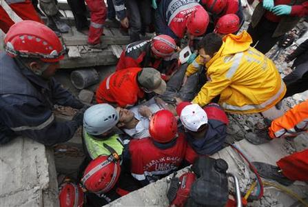 Emergency service workers carry an earthquake survivor during rescue operations in Ercis, near the eastern Turkish city of Van, October 24, 2011. REUTERS/Osman Orsal