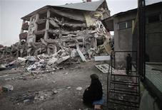 <p>A woman sits near a building that collapsed after the earthquake in Ercis October 26, 2011. REUTERS/Morteza Nikoubazl</p>
