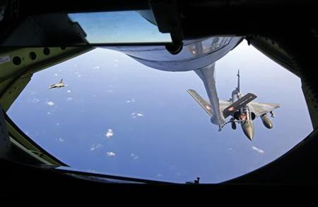 A French Mirage 2000 fighter jet (R), accompanied by a French Rafale (L), refuels with an airborne Boeing C-135 refuelling tanker aircraft from the Istres military air base during a refuelling operation above the Mediterranean Sea March 25, 2011. REUTERS/Jean-Paul Pelissier